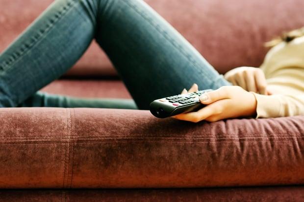 Closeup image of a female hand holding remote control.jpeg